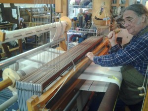 Artisan using a loom to create fabric with a weave/pattern for the upcoming Christmas season. The control mechanism is fairly complex that allows the flying shuttle and the proper heddles in place.
