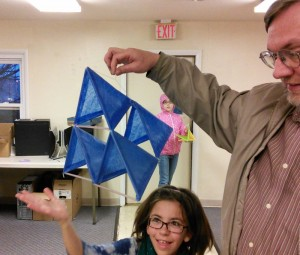 Brian holds up his completed kite by the bridle. He used just one longer string for the bottom layer, the rest of us built individual cells and tied them together.