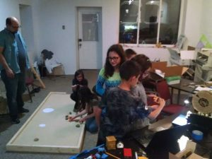 """Second team works on layout at the makerspace, while another team admires the """"zombie fish"""" being printed for Halloween."""
