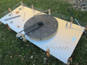 Time Turner, a steam-punk hole built by 11-12 year old kids, used a BBQ rotisserie motor and old bicycle inner tube to rotate the clock face (which has a paddle underneath). The pulley and golf ball tee were 3D printed & the clock numbers were cut using the Makerspace laser cutter.