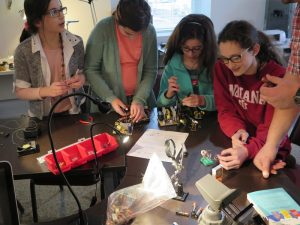 A group of the girls at the meeting assemble the parts mostly scavenged from other electronics.